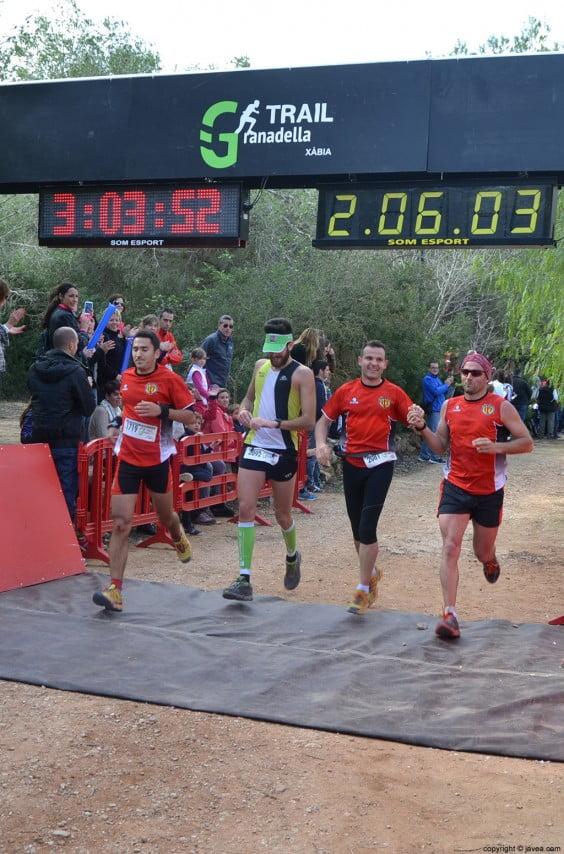 Grupo de corredores cruzando la línea de meta juntos