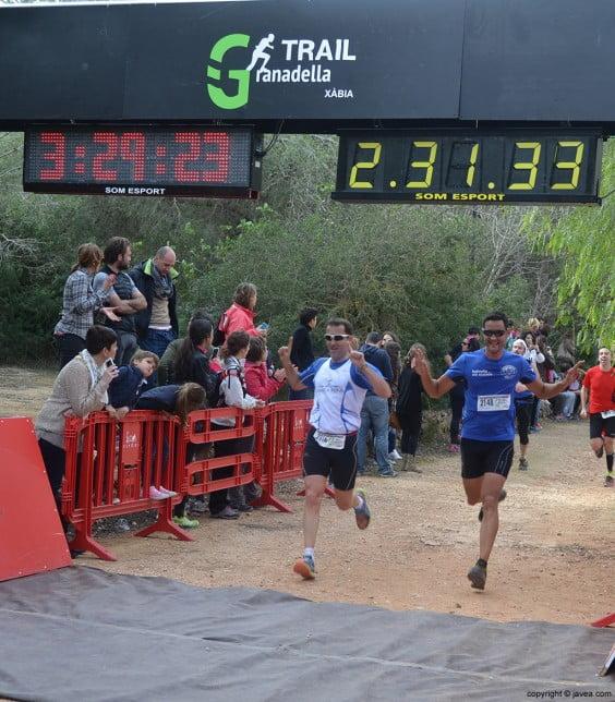 Pareja de corredores cruzando la línea de meta