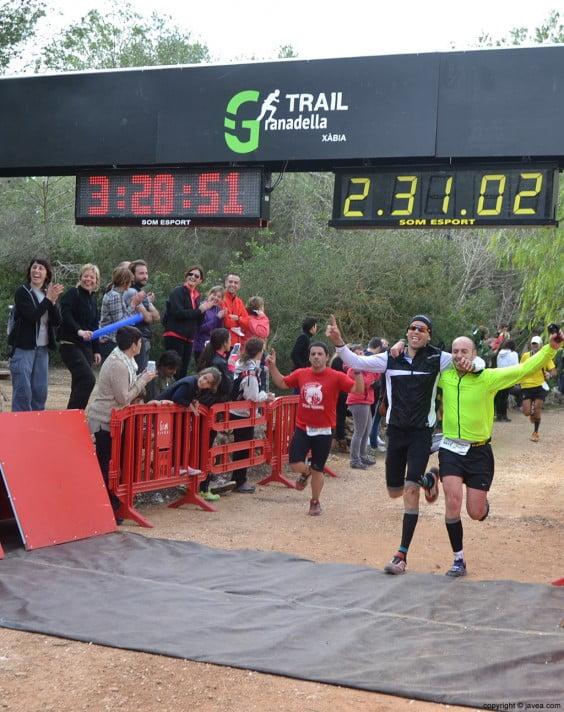 Pareja de corredores cruzando la línea de meta situada en el Parque de Pinosol de Jávea
