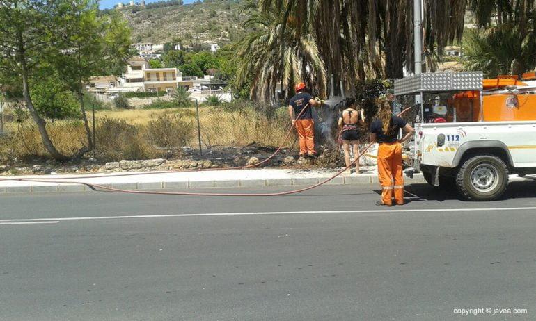 Un miembro de Protección Civil con la manguera apagando el fuego
