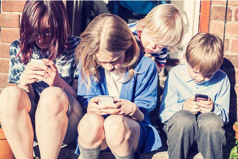 Niños utilizando el teléfono móvil