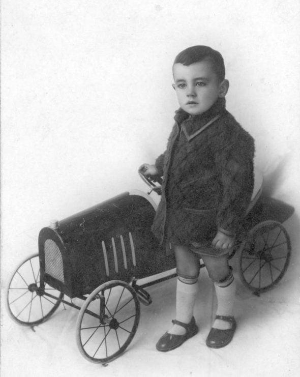 Niño junto a un coche de juguete