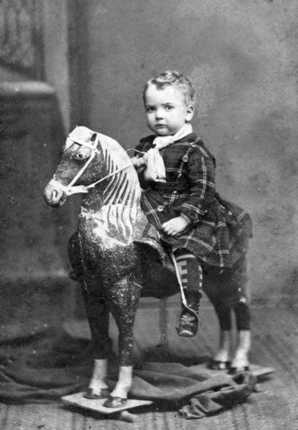 Niño subido al caballo de cartón