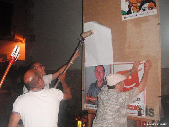 Miembros de Compromís pegando un cartel