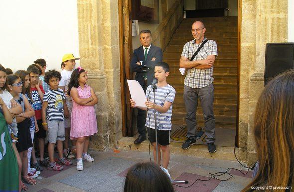 Niño leyendo manifiesto de bienvenida a la badera dels Tradijocs