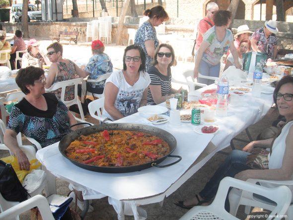 Grupo de amas de casa ante una paella