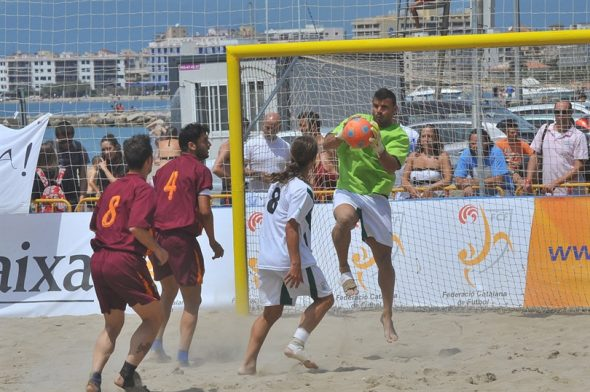 Portero blocando un balón en un choque de fútbol playa