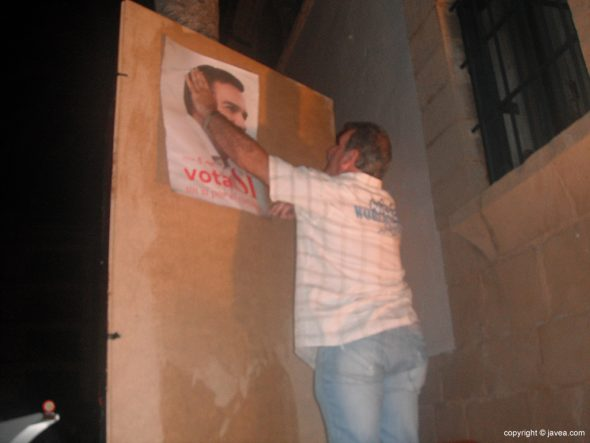 Un simpatizante socialista colocando un cartel