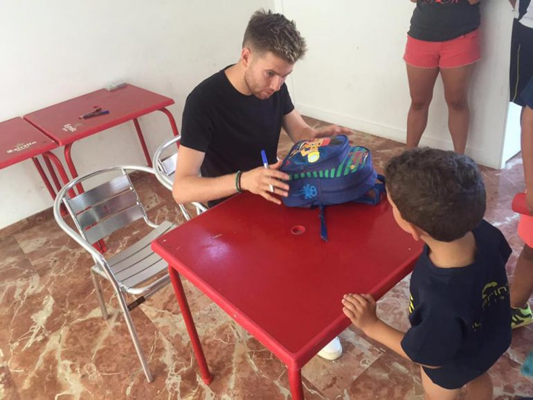 Adrián Ortolá firmando una mochila