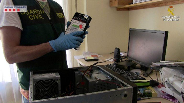 Guardia Civil con un disco duro en la mano