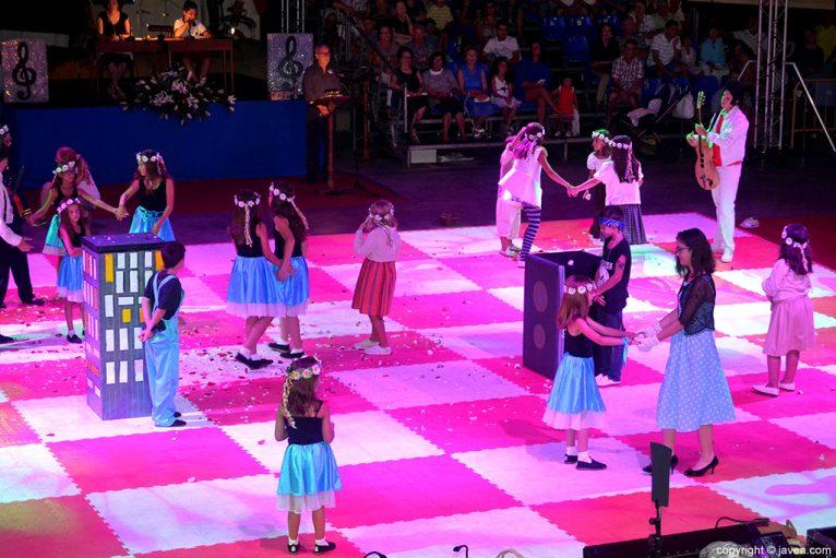 Los niños y niñas participantes bailando sobre el tablero durante la representación