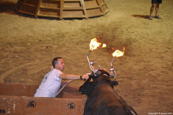 Miembro de la cuadrilla d'emboladors El Trençat cortando la cuerda del toro