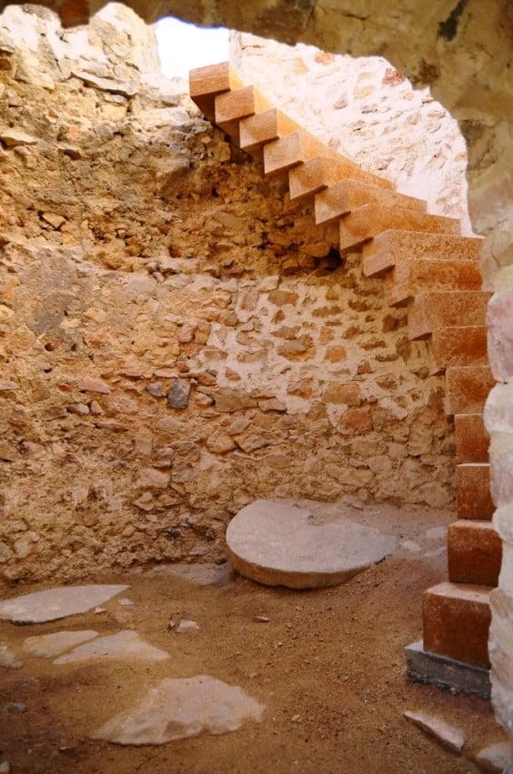 Interior del molí nombre 2 on s'aprecia part de la mola i l'escalinata al segon pis