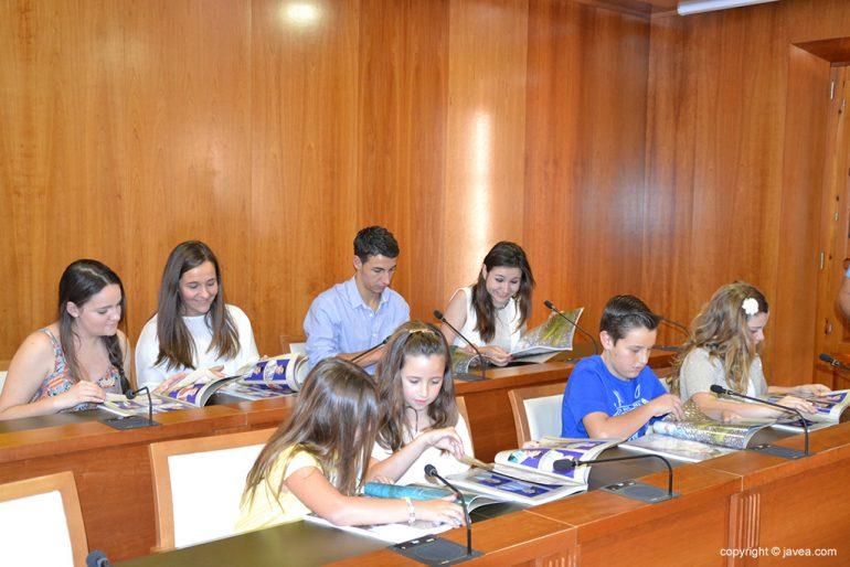 Miembros de la Comisión infantil y quintos hojeando el libro de fiestas de Fogueres