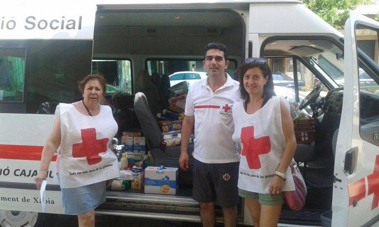 Voluntarios con la ambulancia cargada de alimentos