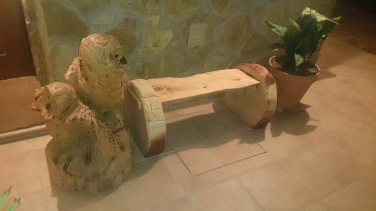 Figura de buhos y bancos hechos tallando troncos