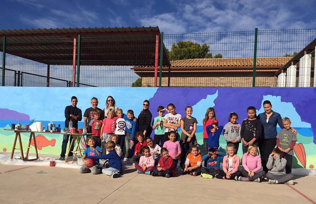 Escolares junto al mural pintando