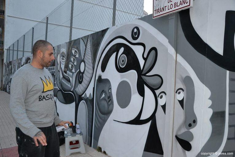 Gabriel López pintando el mural