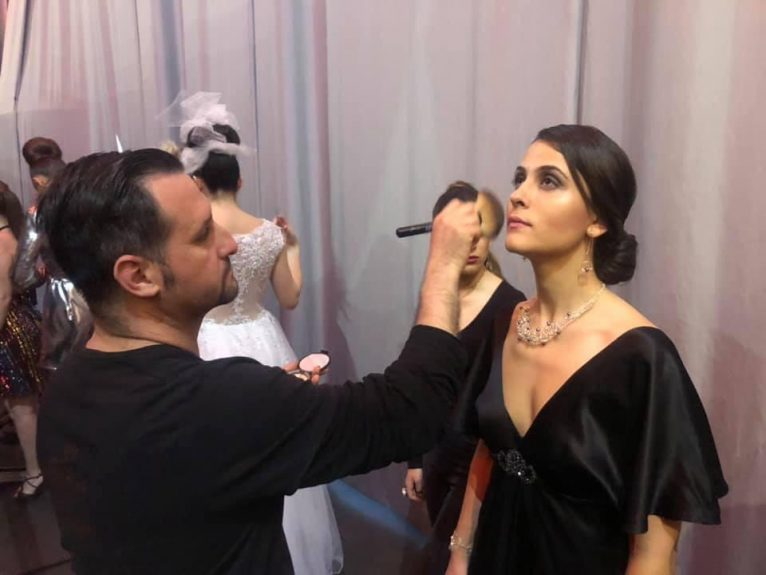 Óscar maquillant a una model en una passarel·la de moda