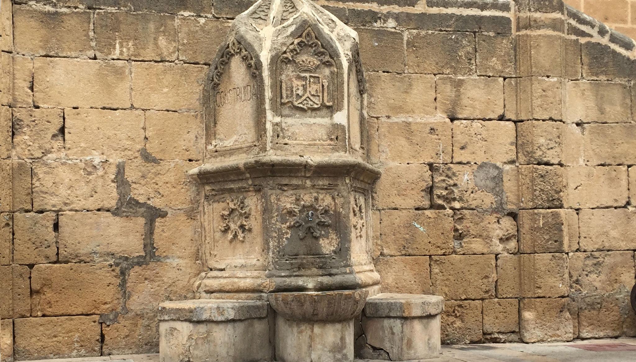 Detalle de la fuente apoyada en la doble escalinata en la Iglesia de San Bartolomé de Jávea