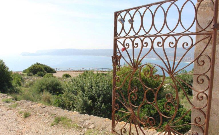 Detalle de una puerta con el mar al fondo, en el mirador del Cap de Sant Antoni