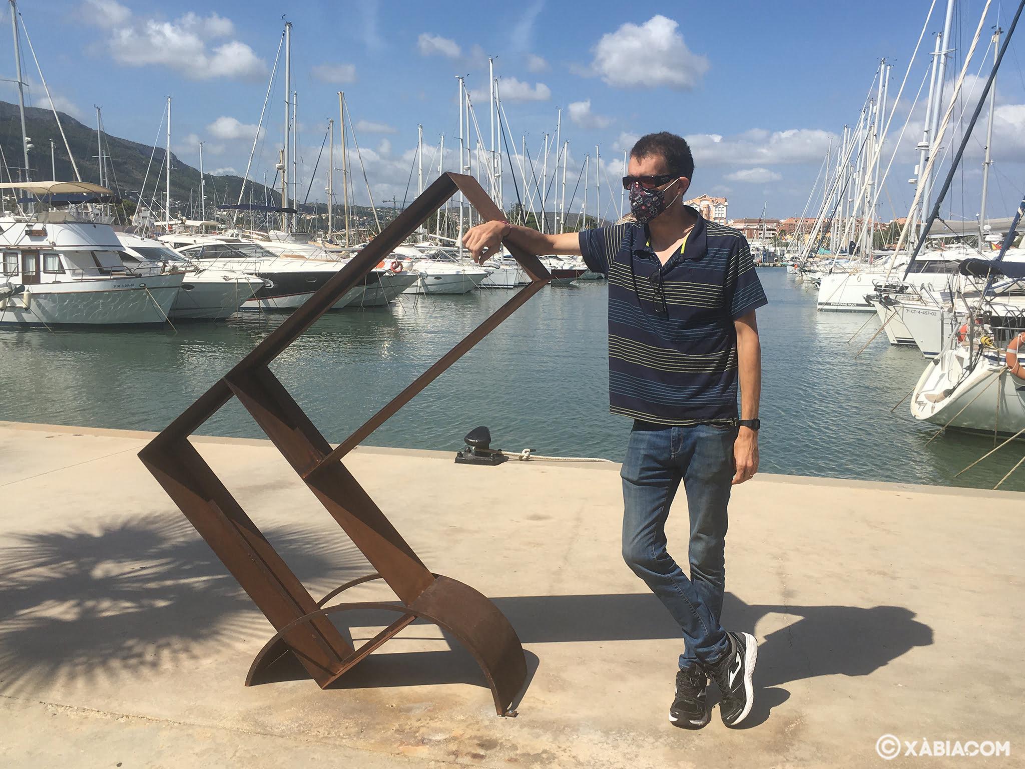 El artista Juan Carava junto a su obra