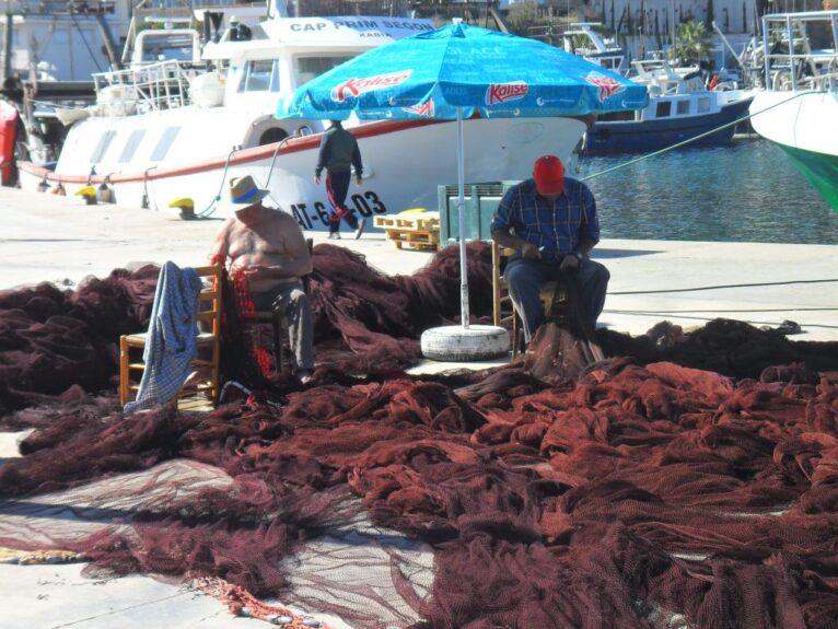 Pescadores cosiendo redes