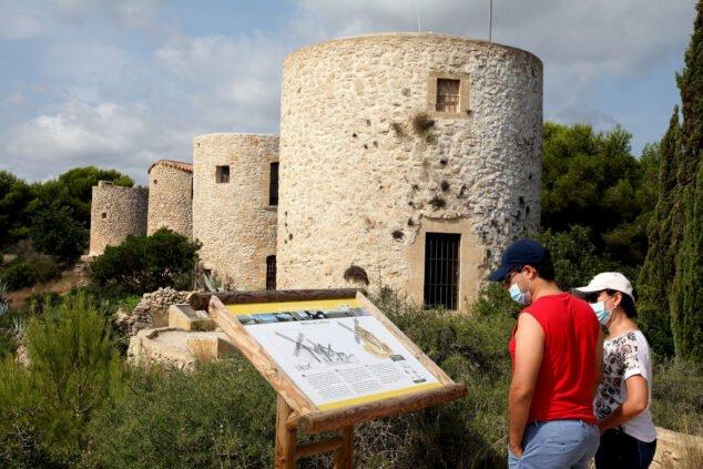 Imagen: Excursionistas mirando el panel informativo de los molinos de La Plana