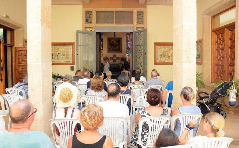 Personas escuchando misa en el exterior del Santuari de la Mare de Déu dels Àngels