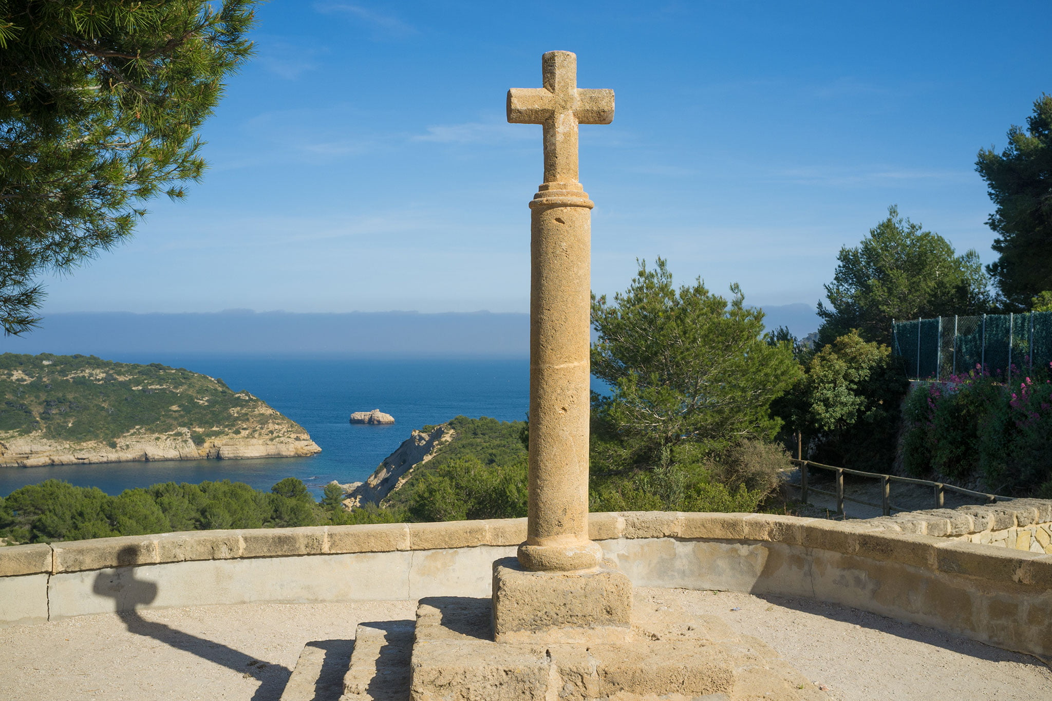 Imagen de la Cruz del Portitxol, con la Isla del Portitxol al fondo