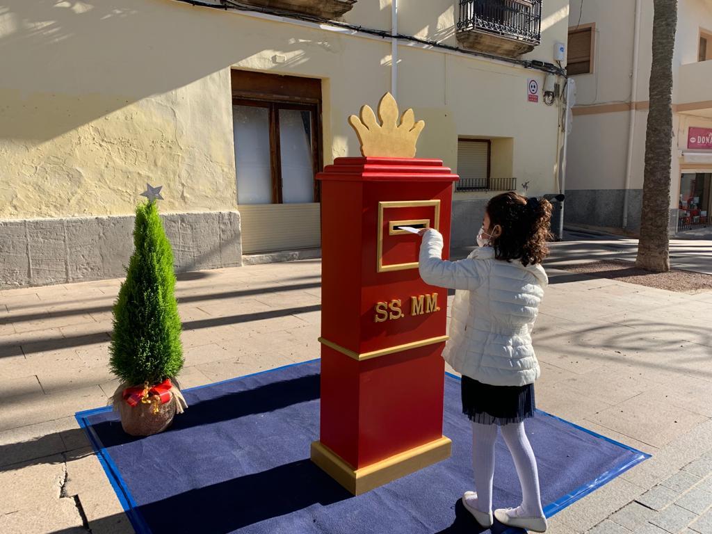 Una niña deposita su carta en el buzón de los Reyes Magos de Oriente