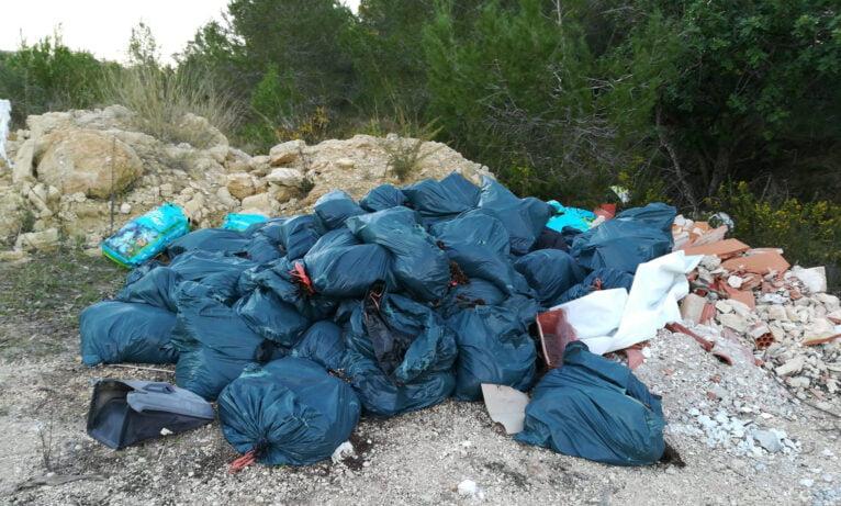 Gran cantidad de bolsas de basura en la parcela privada