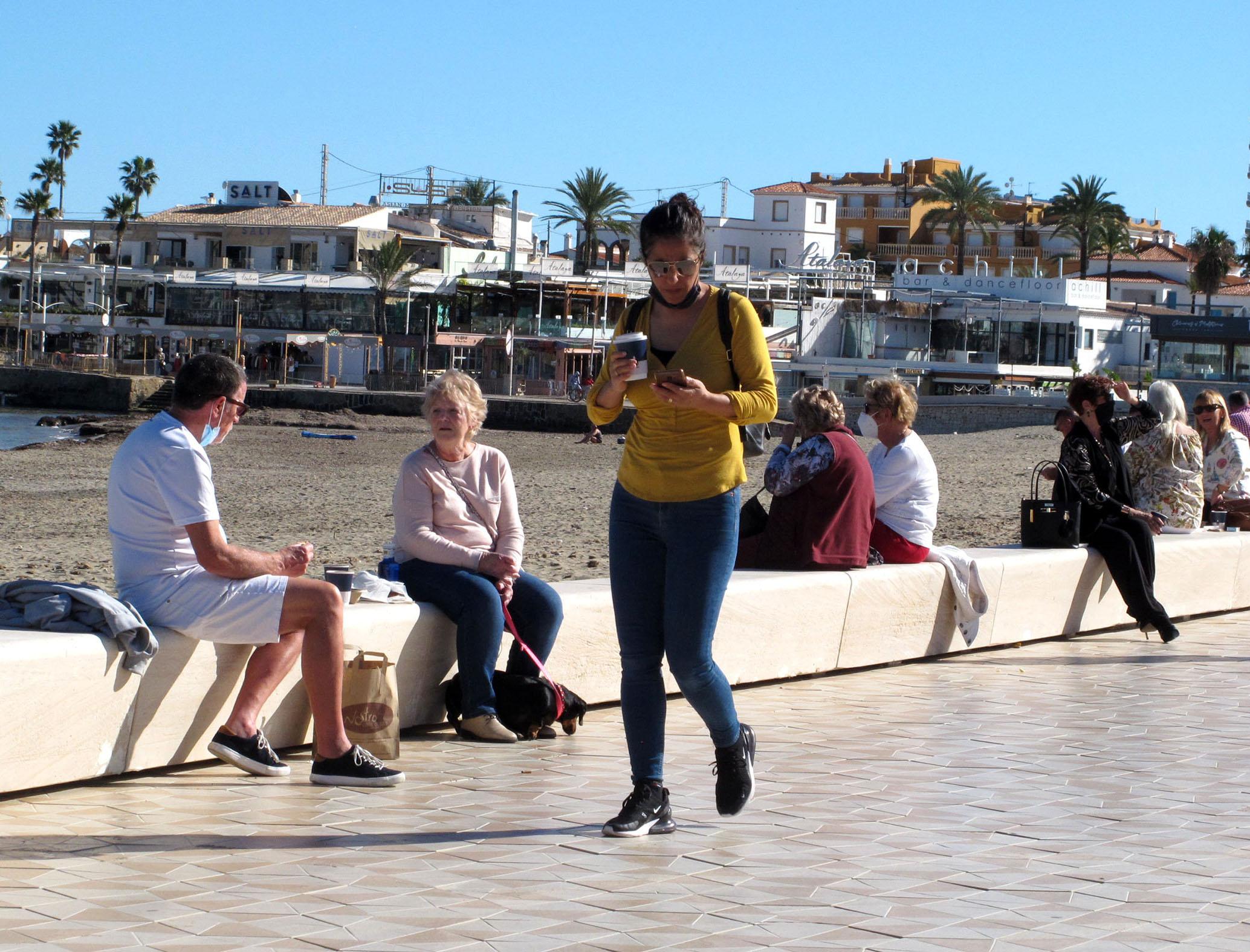 Mujer paseando con café en la playa del Arenal