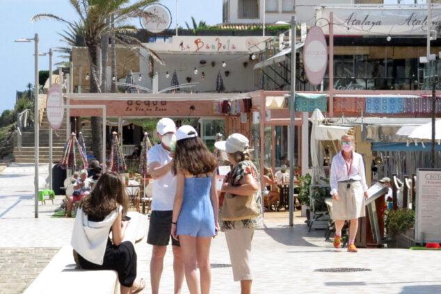 Imagen: Turistas con mascarilla en el paseo de la playa del Arenal