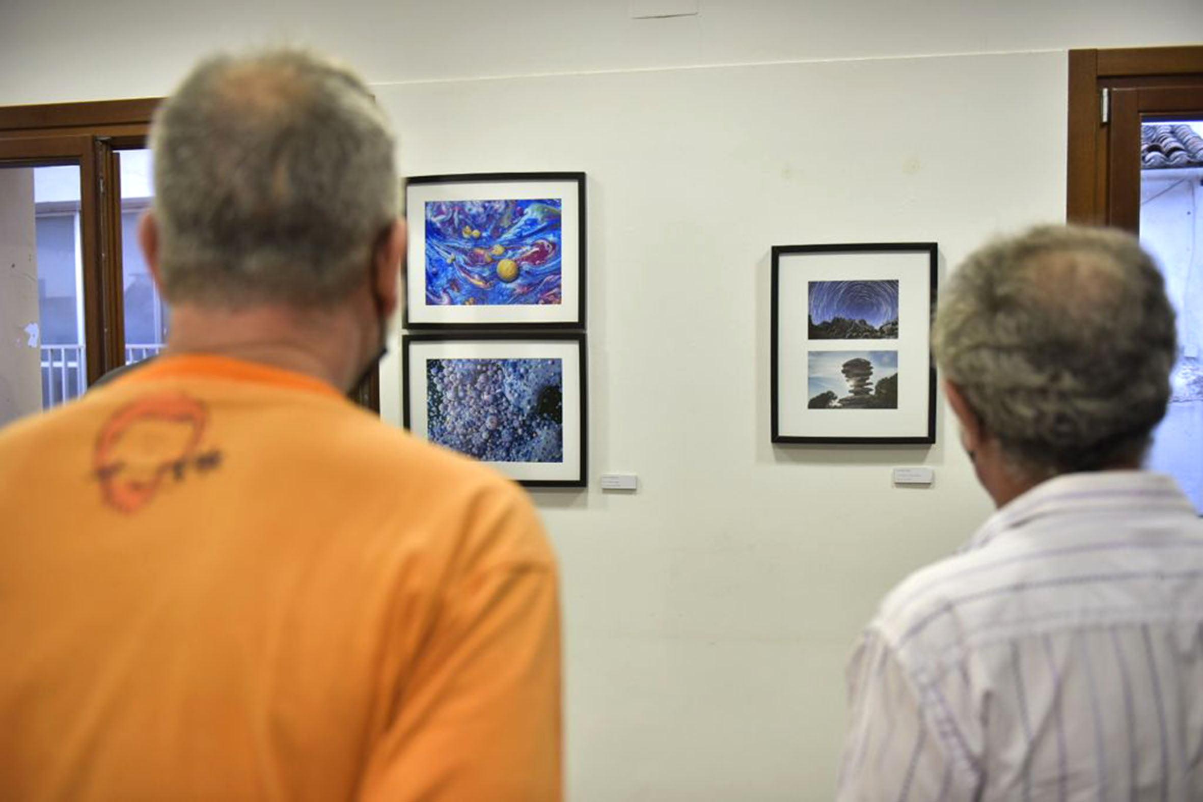 Público observando algunas fotografías de la exposición