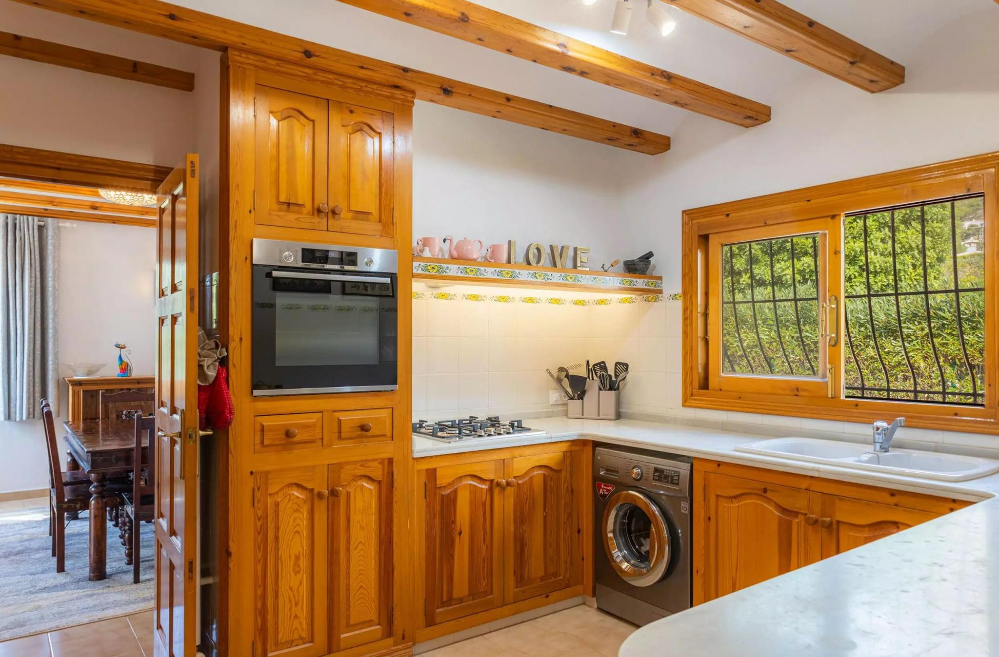 Cocina con vistas en villa familiar con Vicens Ash Properties