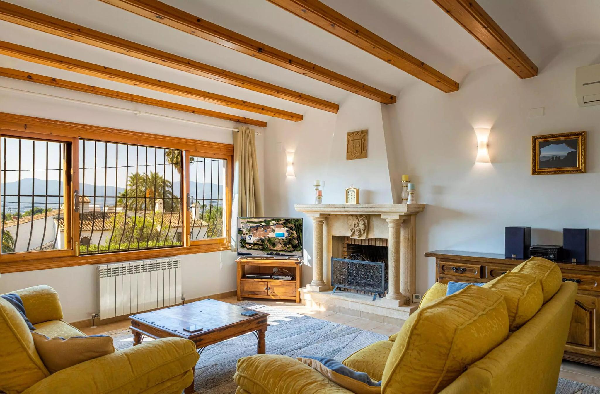 Salón amplio con chimenea en villa familiar con Vicens Ash Properties